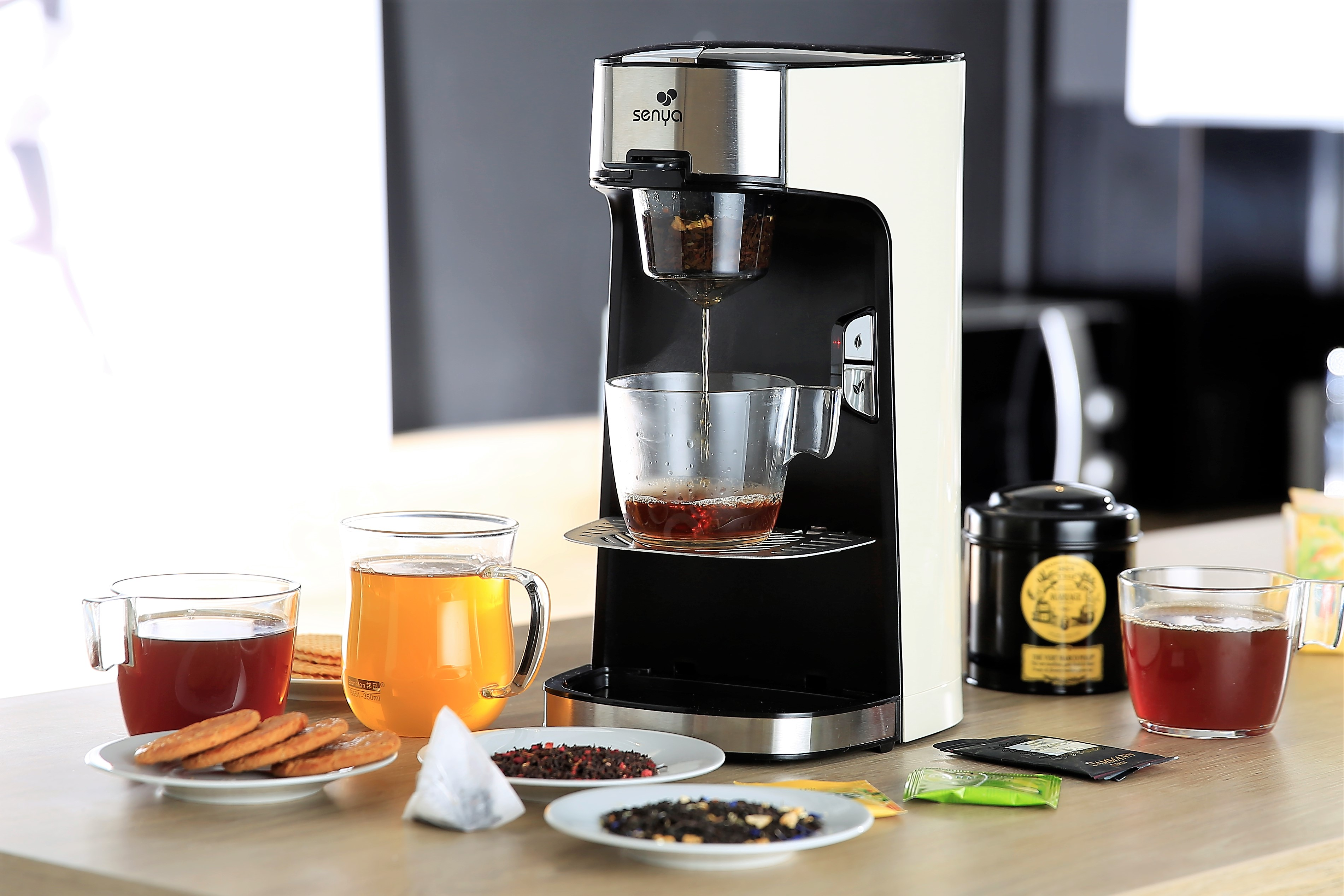 Machine à thé électrique, théière électrique vu de profil sur une table de cuisine