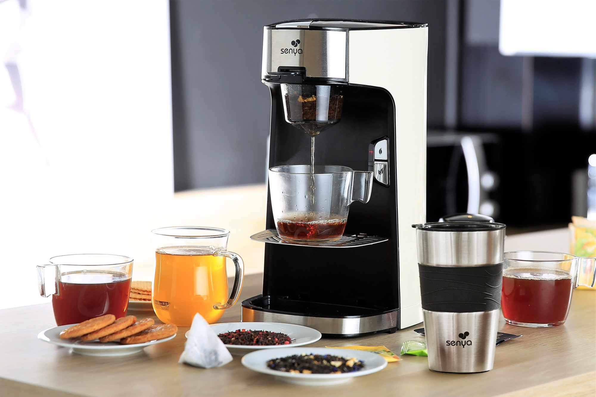 Machine à thé noir avec le mug isotherme posé à côté, le tout sur un plan de travail